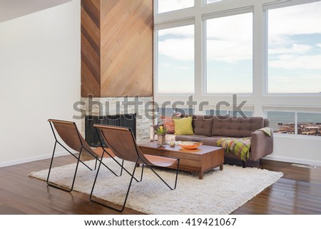 Amazing contemporary living room with hardwood floors, rug and vaulted ceiling in new luxury home. View of Kitchen, entryway, and second story loft style area. - stock photo