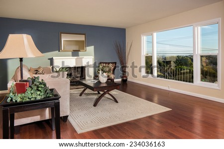 Amazing contemporary living room with view window, framed fire place, rug, table, wooden floor and accent wall in blue.  - stock photo