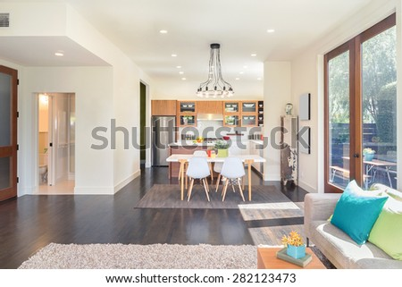 Amazing contemporary luxurious home with kitchen table in contemporary home with large windows and double french doors surrounded by trees. Hardwood floor with hand-woven natural fine sisal rug. - stock photo