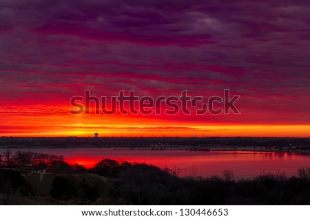 Amazing crimson/red sunrise over Benbrook Lake in Fort worth, TX - stock photo