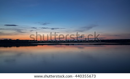 amazing dusk at a sunset with colors reflecting in the water of a lake - stock photo