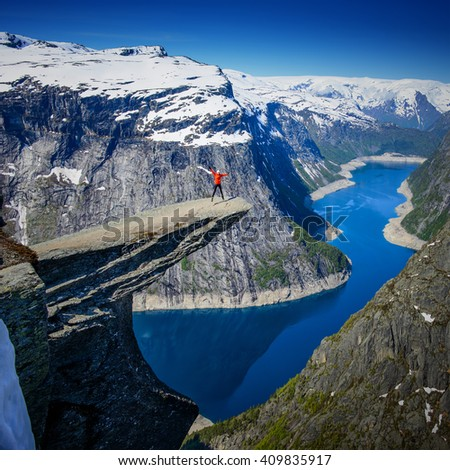 Amazing Famous Norway Trolltunga view point at morning with snow at the top of mountain - stock photo