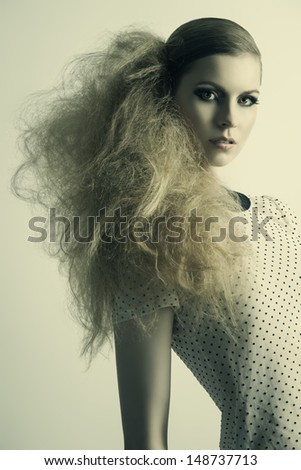 amazing fashion portrait of blonde pretty girl with strange modern hair-style and dark make-up, wearing pois shirt       - stock photo