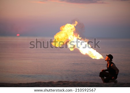 Amazing fire-breathing on the beach at sunset - stock photo