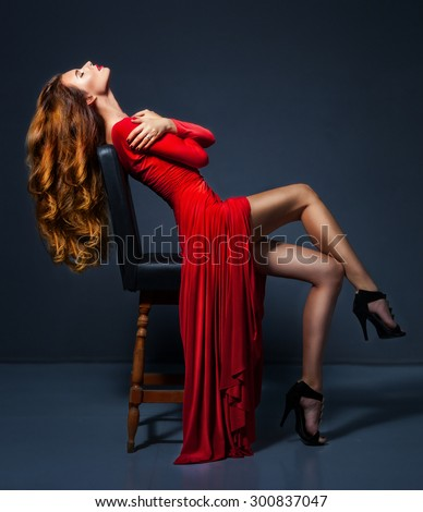 Amazing glamour woman in long red dress sitting at the chair. Evening make up and hairstyle. Fashion portrait. Studio shot. - stock photo