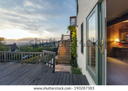 Amazing inside out view from craftsman bedroom towards large long balcony exterior with table and chairs and lake view at twilight. - stock photo