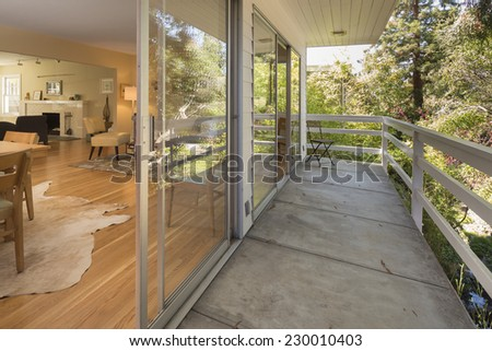 Amazing inside out view from craftsman living room with large long balcony exterior surrounded by trees.  - stock photo