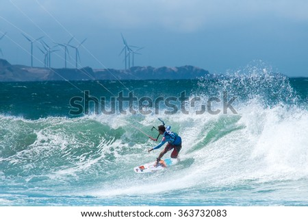 Amazing kite surfing at Philippines. Processional instructor surfing in ocean waives near windmills - stock photo