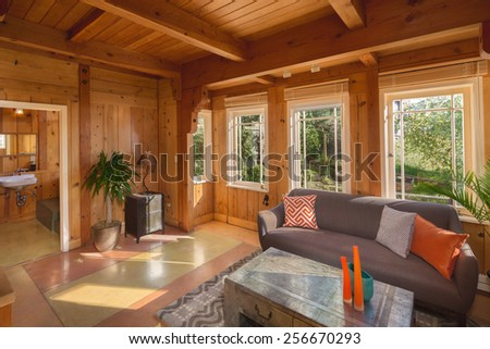 Amazing Living Room in all wood, with couch and pillows, table, chest, rug, craftsman style with adjacent bathroom. - stock photo