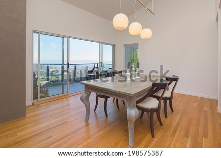 Amazing modern dining area of hillside home with sliding glass doors leading to outdoors with balcony and breathtaking incredible view. - stock photo