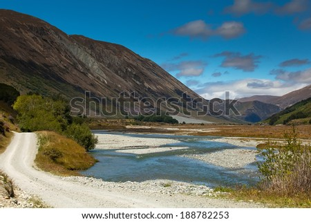 Amazing mountains and river water near a gravel road winding through the pass going to Queenstown in New Zealand. - stock photo
