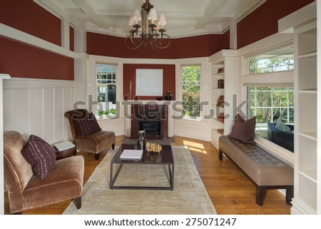 Amazing Music room or Library in red, white in traditional home with chandelier, dual chairs with rug, fire place and view window to enclosed porch. - stock photo