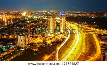 Amazing nightscape of Ho chi Minh city, Vietnam from high view, city bright in yellow electric light, trail on road, landscape of new urban in radiant colors at night - stock photo