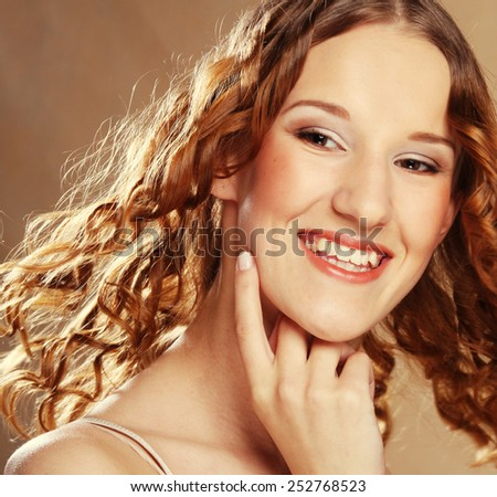 Amazing portrait of beautiful young woman with curly hair. Close-up face studio photo. - stock photo
