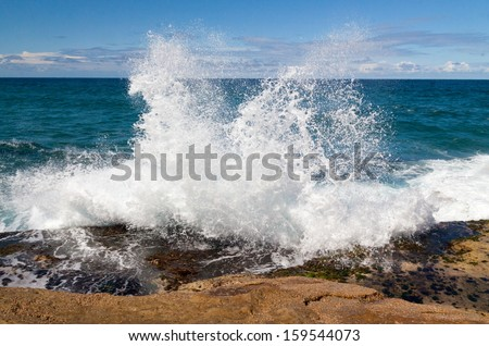 Amazing power of waves crashing against the rocks - stock photo