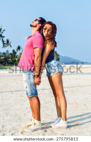Amazing pretty young hipster couple in love going crazy and having fun at summer vacation near ocean, smiling and shoving tongue, happiness and freedom. - stock photo