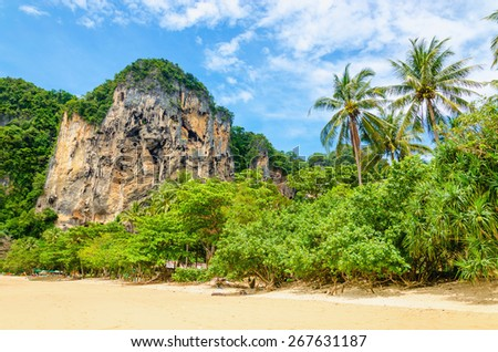 Amazing Railay Beach with mogotes, long tail boat and high palm trees, Krabi, Thailand - stock photo