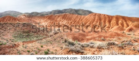 Amazing scenic panoramic view orange hills, screes of sandstone, sides carved away by erosion, canyon Uchterek, Kyrgyzstan. - stock photo