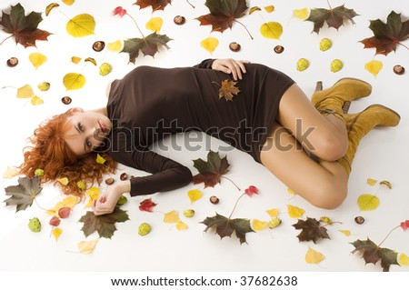 amazing shot of red haired woman laying down on white floor with autumn leaves all around - stock photo
