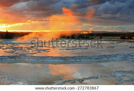 Amazing sunset above a steaming geyser in Yellowstone, Wyoming, USA. - stock photo
