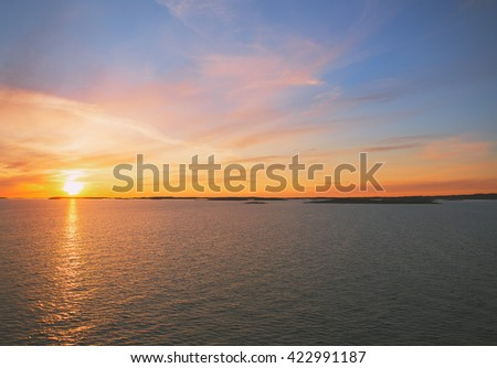 Amazing sunset by the sea. The sun is about to go down behind the sea. The sun is composed to the left. Image has a vintage effect applied. - stock photo