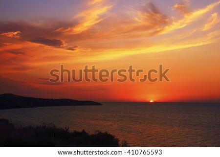 Amazing sunset scenery - dawning sun, coast silhouette and rippled water against the background of dramatic cloudy sky at Azov Sea, Taman, Krasnodar Krai, South Russia - stock photo