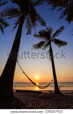 Amazing sunset seen from under palm trees on Kamala beach in Phuket Thailand - stock photo