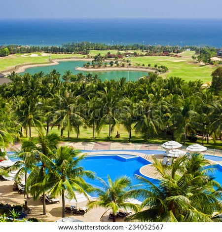 Amazing top view on swimming pool and golf field at tropical luxury hotel near ocean - stock photo
