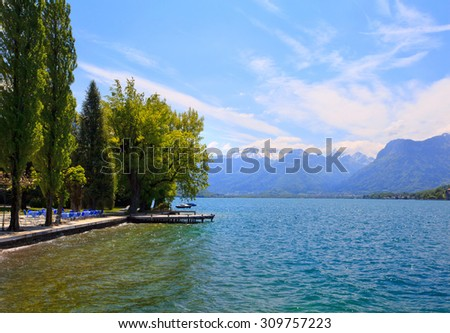 Amazing view above Annecy Lake (France), with a calm shore and trees - stock photo