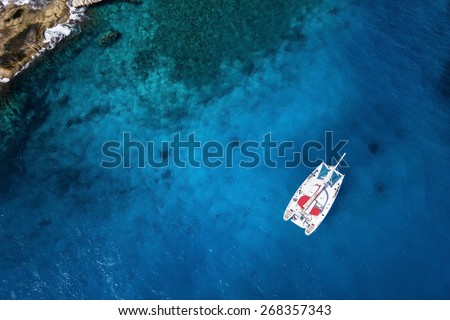 Amazing view to Catamaran cruising in open sea at windy day. Drone view - birds eye angle Coco Island. - stock photo