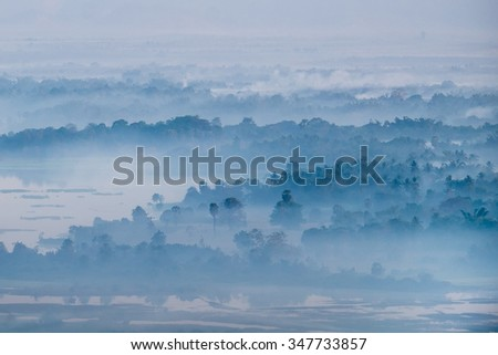 Amazing watercolor view of foggy morning landscape with farm fields at Thanlwin river. Hpa An, Myanmar (Burma) travel landscapes and destinations - stock photo