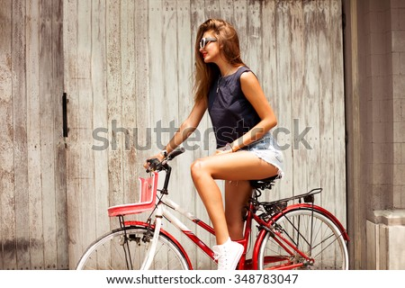 amazing  woman ride bicycle and wear boho chic outfit,denim clothes,hipster girl,sunglasses fashion,urban street style,soft vintage colors,rider retro bicycle.music lounge,relax - stock photo