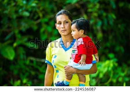 AMAZONIA, PERU - NOV 10, 2010: Unidentified Amazonian woman carries her son on arms. Indigenous people of Amazonia are protected by  COICA (Coordinator of Indigenous Organizations of the Amazon Basin) - stock photo