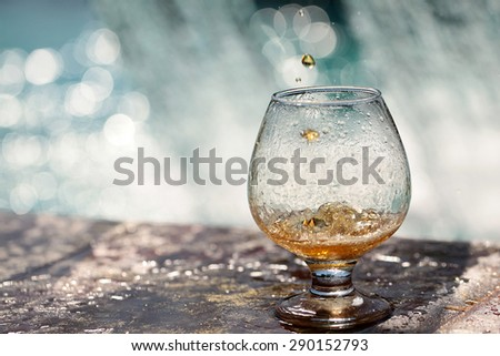 Amber alcoholic drink poured in glass stnading on stone rim of fountain on water splashes background copyspace, horizontal picture - stock photo