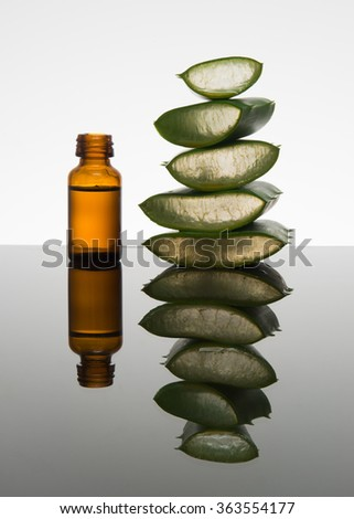 Amber bottle with aloe vera leaf cut into pieces and dropper - stock photo