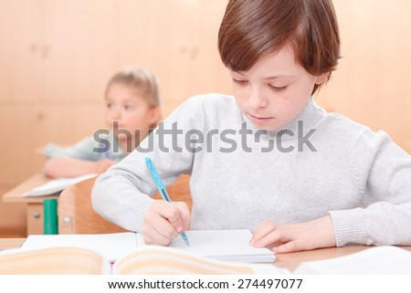 Ambitious boy. Little boy writing something in his copy book during classes. - stock photo