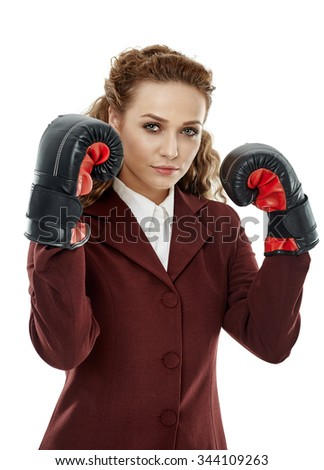 Ambitious businesswoman with her boxing gloves on, ready to fight - stock photo