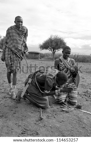 AMBOSELI, KENYA-OCT. 13: Portrait of young Maasai warriors showing how they make fire in a traditional way to guests visiting their village taken on Oct 13, 2011 in Masai Mara, Kenya. - stock photo