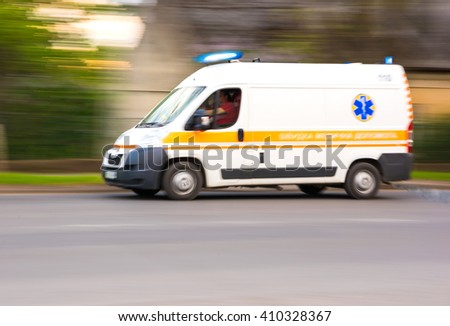 Ambulance in motion driving down the road. Intentional motion blur - stock photo