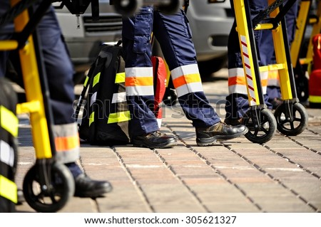 Ambulance personnel feet are seen next to emergency equipment - stock photo