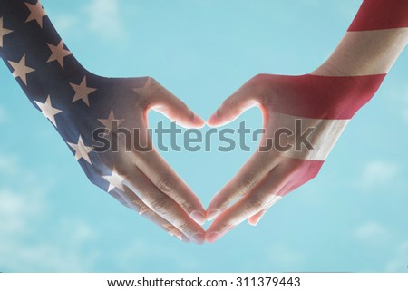 America flag pattern on people hands in heart shaped form against vintage sky background: Happy labor day, Patriot day, USA Independence day, Columbus day , Constitution and citizenship day concept - stock photo