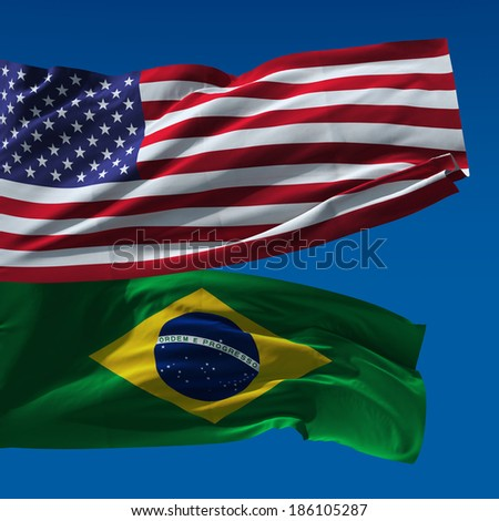 American and Brazilian national flags waving upon blue sky - stock photo