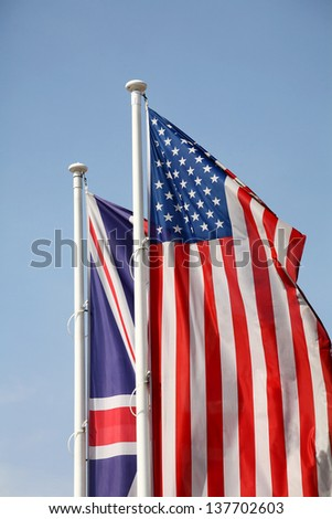 American and British national flags waving upon blue sky - stock photo