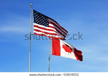 American and Canadian flags flying side by side at the International Flag Plaza in Port Huron, MI - stock photo