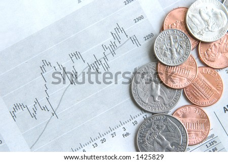 American coins on top of a stock diagram in the financial newspaper. - stock photo