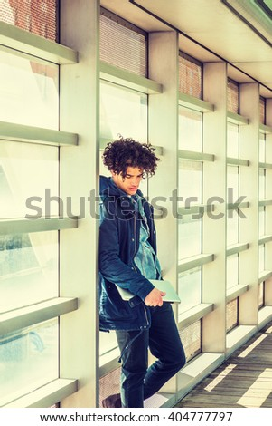 American college student studying in New York. A guy with freckle face, curly long hair, holding laptop computer, standing on walkway, against glass wall on campus, looking down, sad, thinking.  - stock photo
