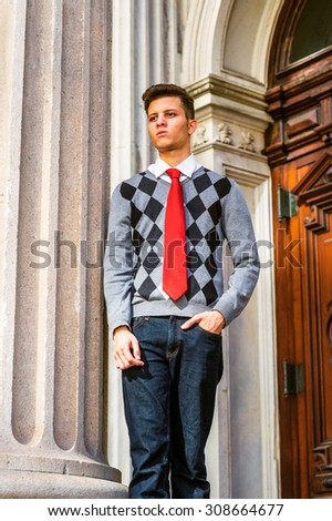 American College Student Studying in New York. Wearing black, white, gray patterned sweater, red necktie, jeans, a young man standing outside vintage style office, sad, thinking, lost in thought.  - stock photo