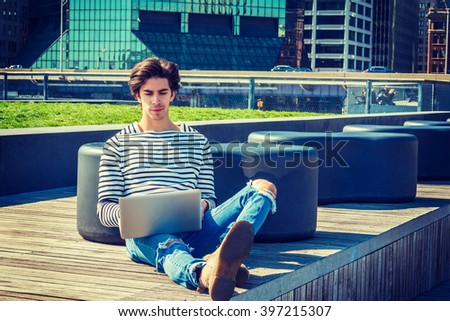 American college student traveling, working in New York, wearing fashionable long sleeve striped T shirt, jeans, sitting on campus, reading, working on laptop computer. Instagram filtered effect. - stock photo