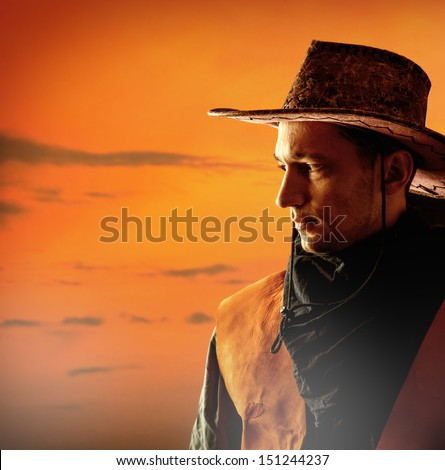 American cowboy in brown hat on a sunset background outdoor - stock photo
