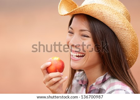 American cowgirl eating peach or nectarine fruit smiling and laughing wearing cowboy hat outside. Healthy eating concept with beautiful young mixed race Caucasian Asian female model outdoor. - stock photo